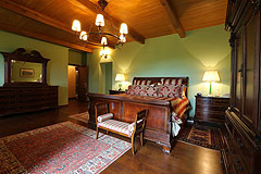 Prestigious Italian villa with Moscato vineyards  for sale in Piedmont. - Master bedroom featuring exposed wooden ceiling
